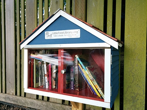 Little Free Library shaped like a blue house