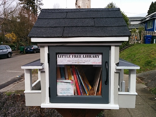 Little Free Library shaped like grey house