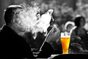 man smoking with a beer in front of him