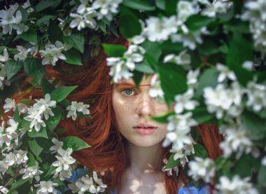 woman looking through flowering tree
