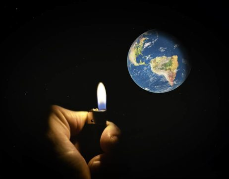 hand holding flame shedding light on Earth